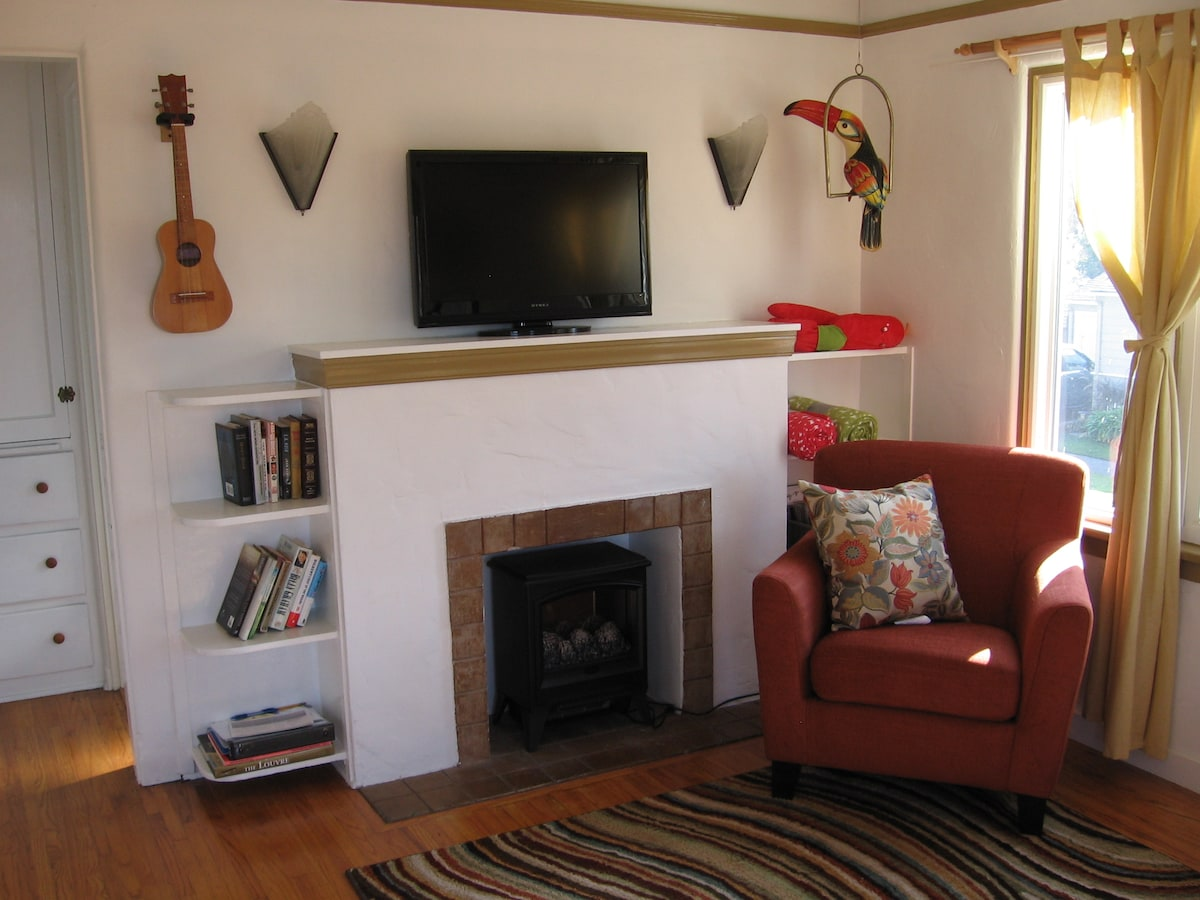 """Enter the front door to find a cozy livingroom, complete with fireplace, TV, comphy love seat and reading chair. Don't be afraid to pick up the uke and hum a few bars, or grab a novel from the """"Book Traders Basket"""""""