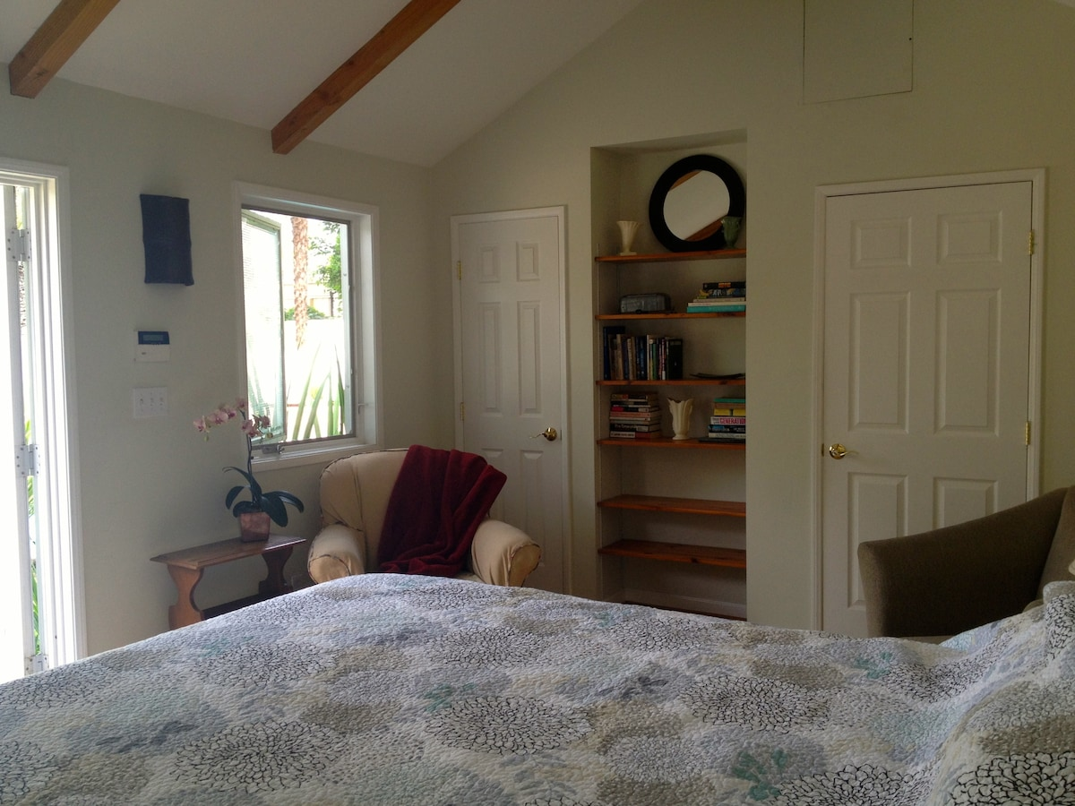 Two comfy chairs for reading, books on the shelf, closet and bathroom.