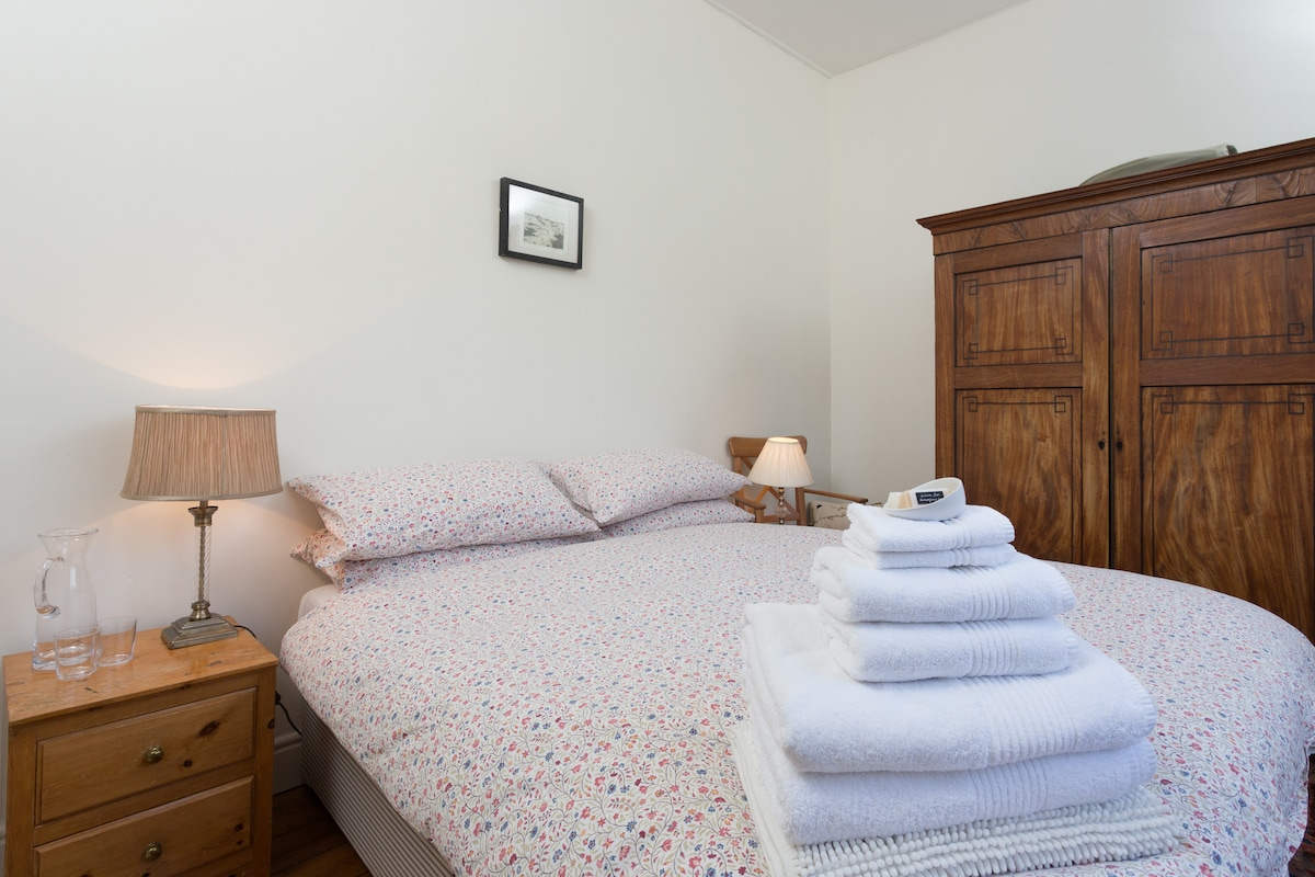 Our small but comfortable bedroom with bedside table, wardrobe, bedside lights and extremely comfortable pocket sprung mattress