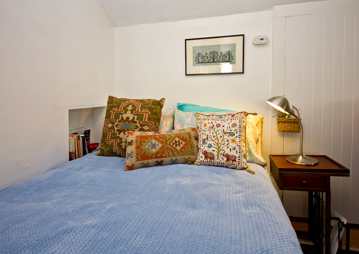 Cozy, full size bed with bedside lamp and alarm clock