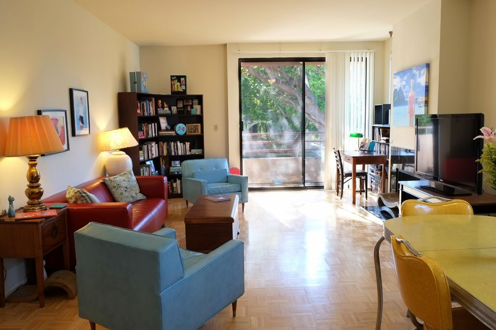 View of the living room from the kitchen. Mid-century chairs meet yellow formica table.