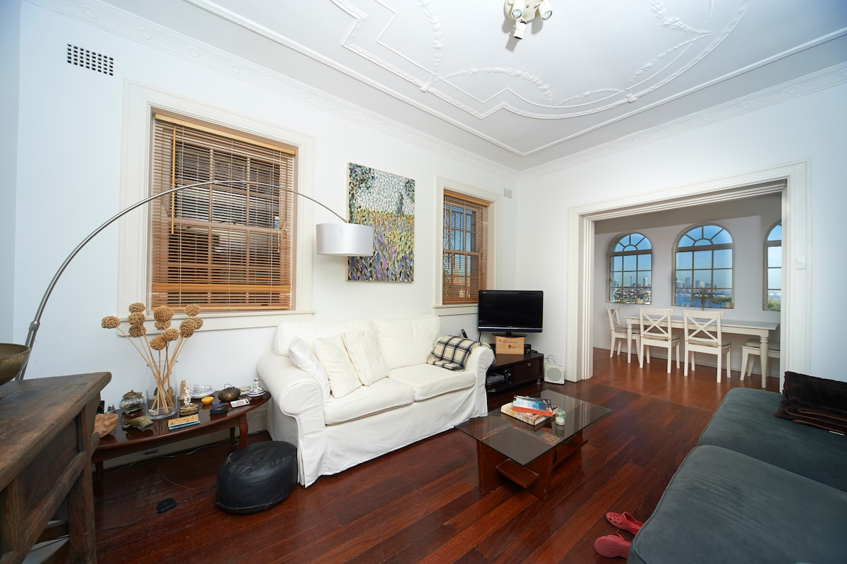 Comfortable living room with artworks and Foxtel, music system, opening directly on to sunroom and harbour views