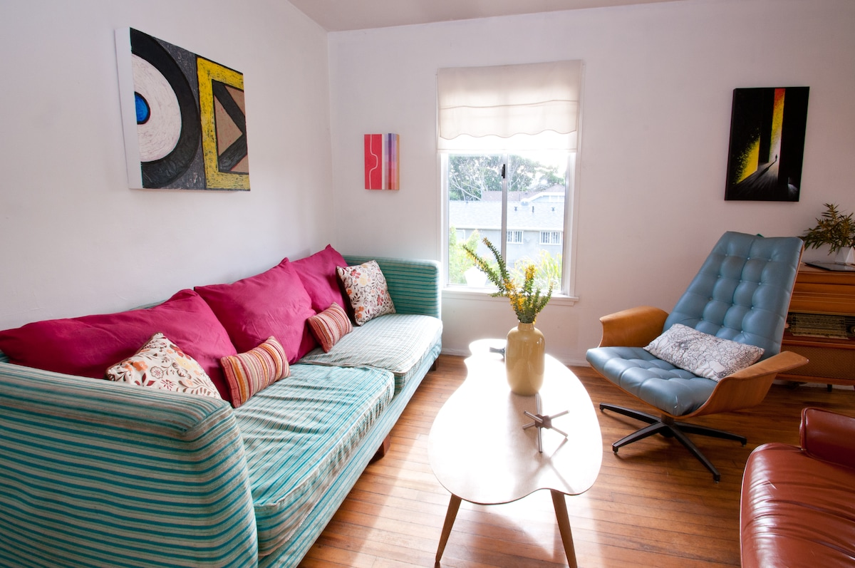 Bright and lively living room. Cozy couch, fluffy pillows and funky art.