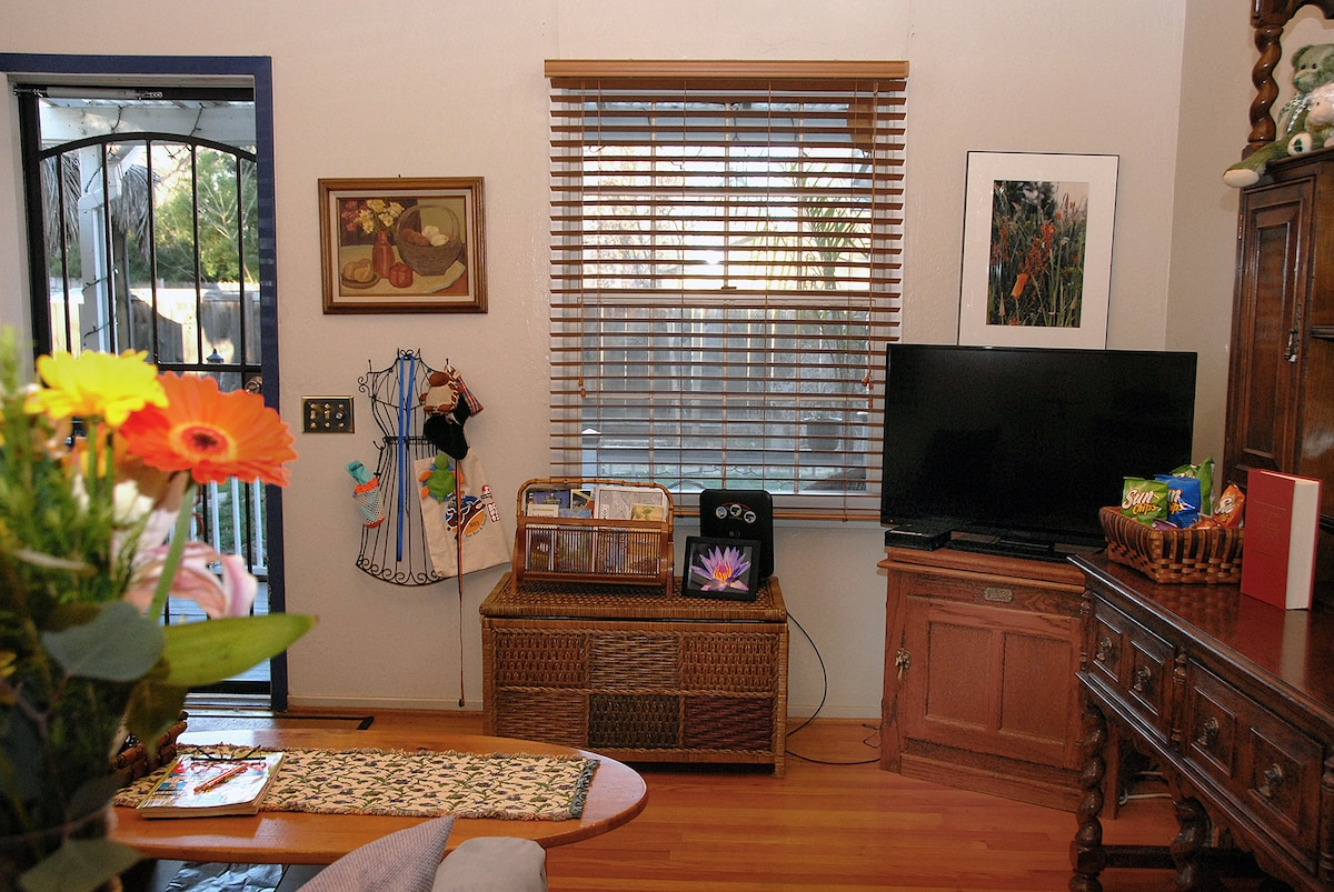 View of the living room with flat screen t.v. and dog accessory hanger near the light/fan switch