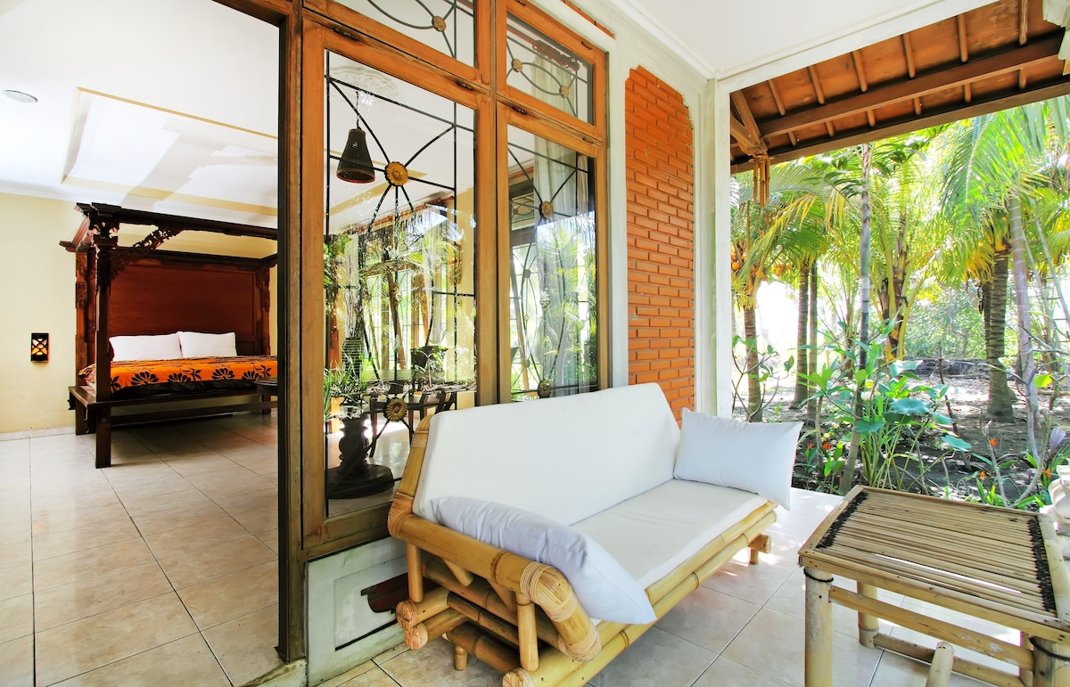 Large porch with 3 seater bamboo sofa and entrance to the apartment, king size bed 1.8 x 2.0 meter ( including musquito net in the frame of the bed ). Surrounded by a quiet/private garden