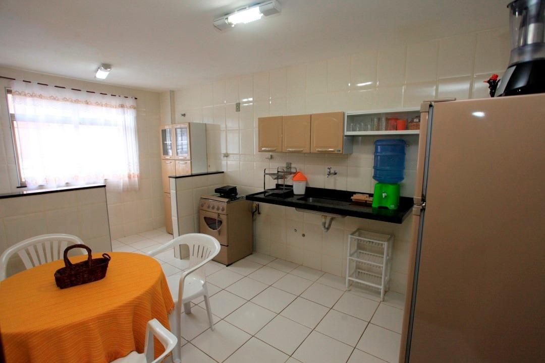Cozinha com fogão, geladeira, armários com pratos, talheres e utensílios, micro-ondas, bem como área com tanque.