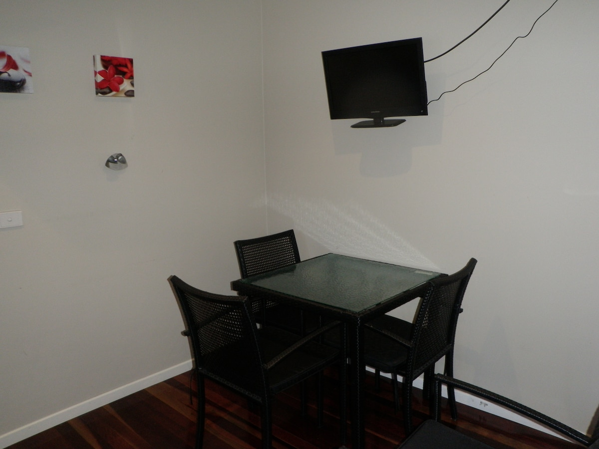 Small dining room table in lounge room. Small TV on wall with foxtel.