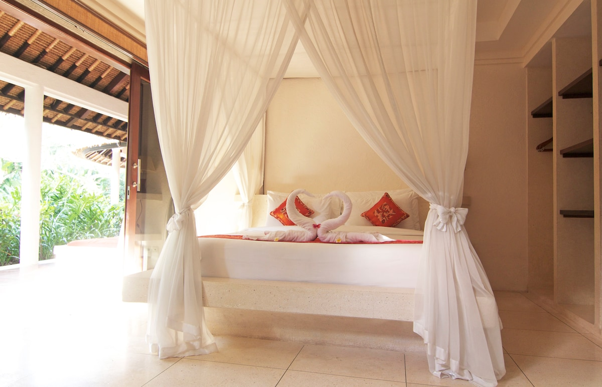 Quality bedding and lush mosquito nets drape King sized beds.