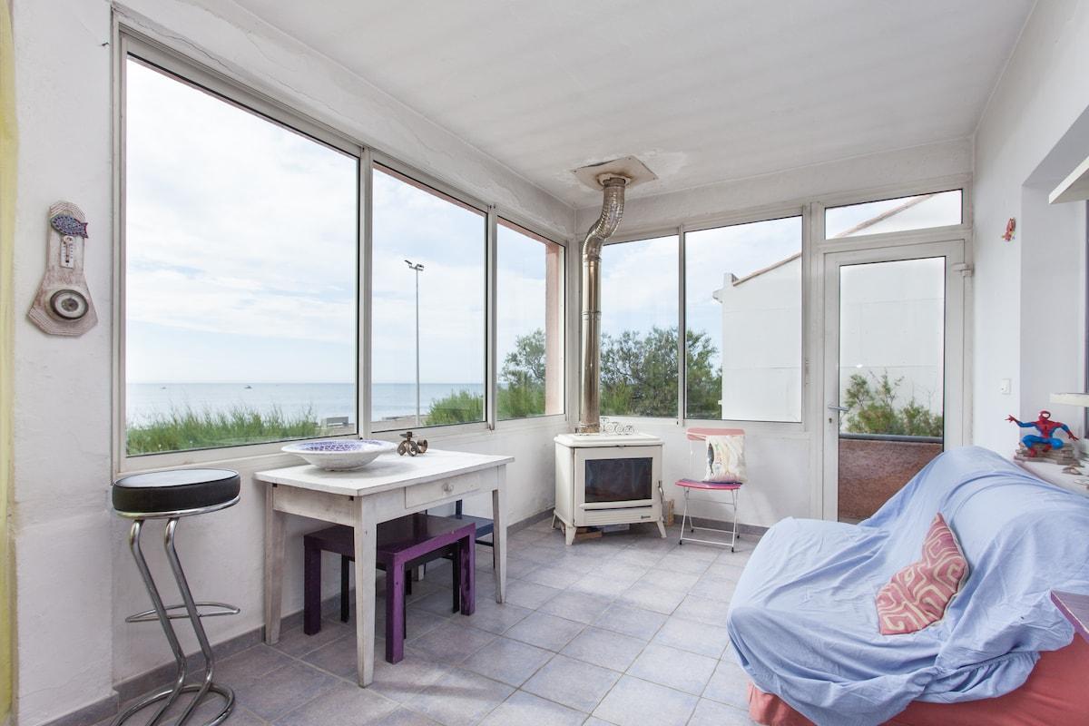 Vaste terrasse avec une cheminé et un canapé avec vue imprenable sur la mer, la plage et l'horizon.