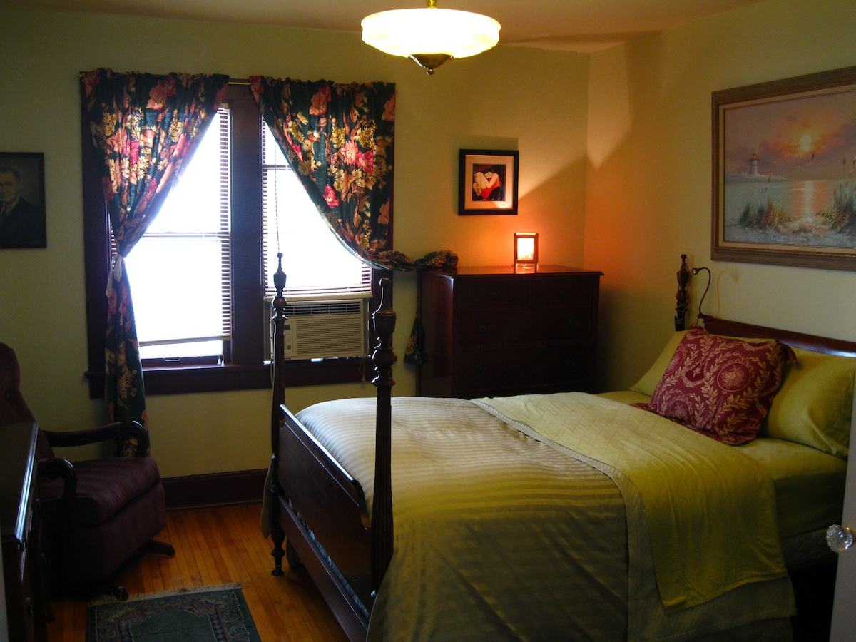 Back bedroom, otherwise known as The Roosevelt Room. Full-size bed, two dressers, AC, rocking chair and closet.