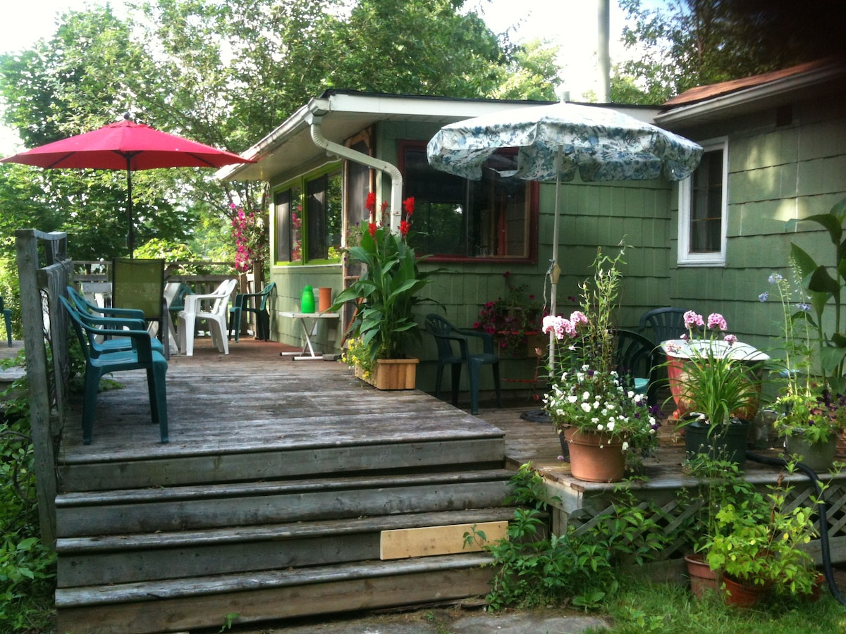 Large deck with large outdoor table and out door tub with hot and cold running water - surrounded by flowers fro privacy