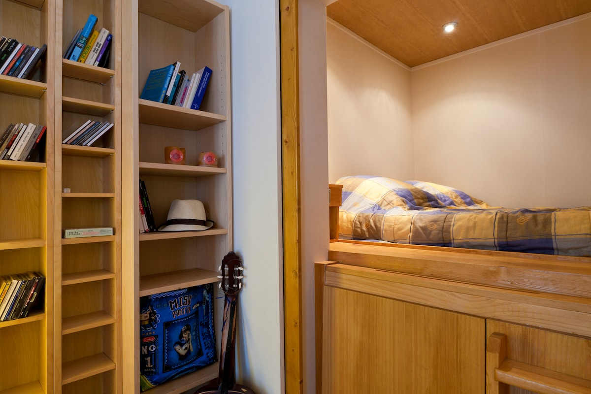 Bedroom entrance. The king size bed is elevated into a stage and occupies the full area of the bedroom.