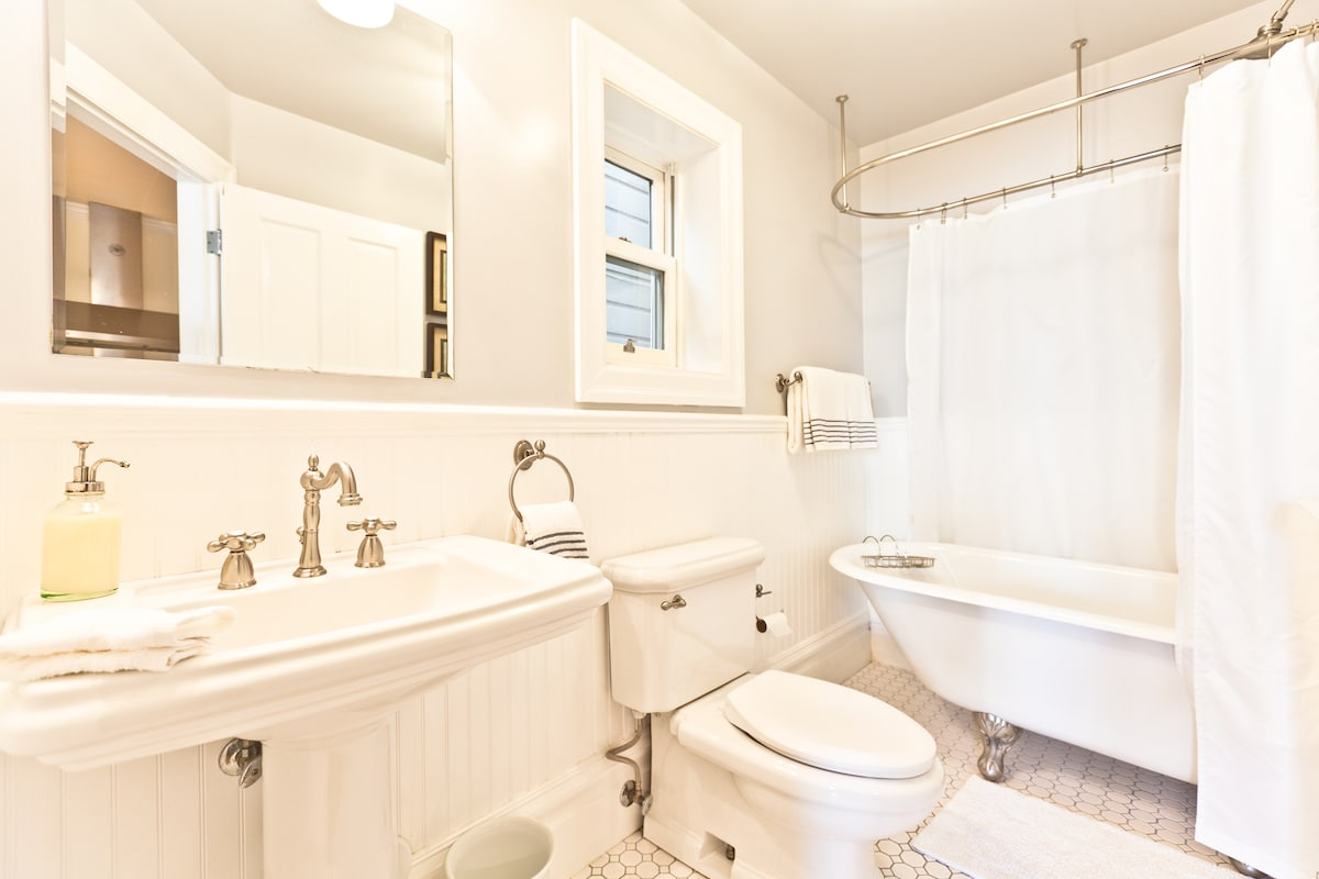 Studio bathroom with clawfoot tub and shower overhead