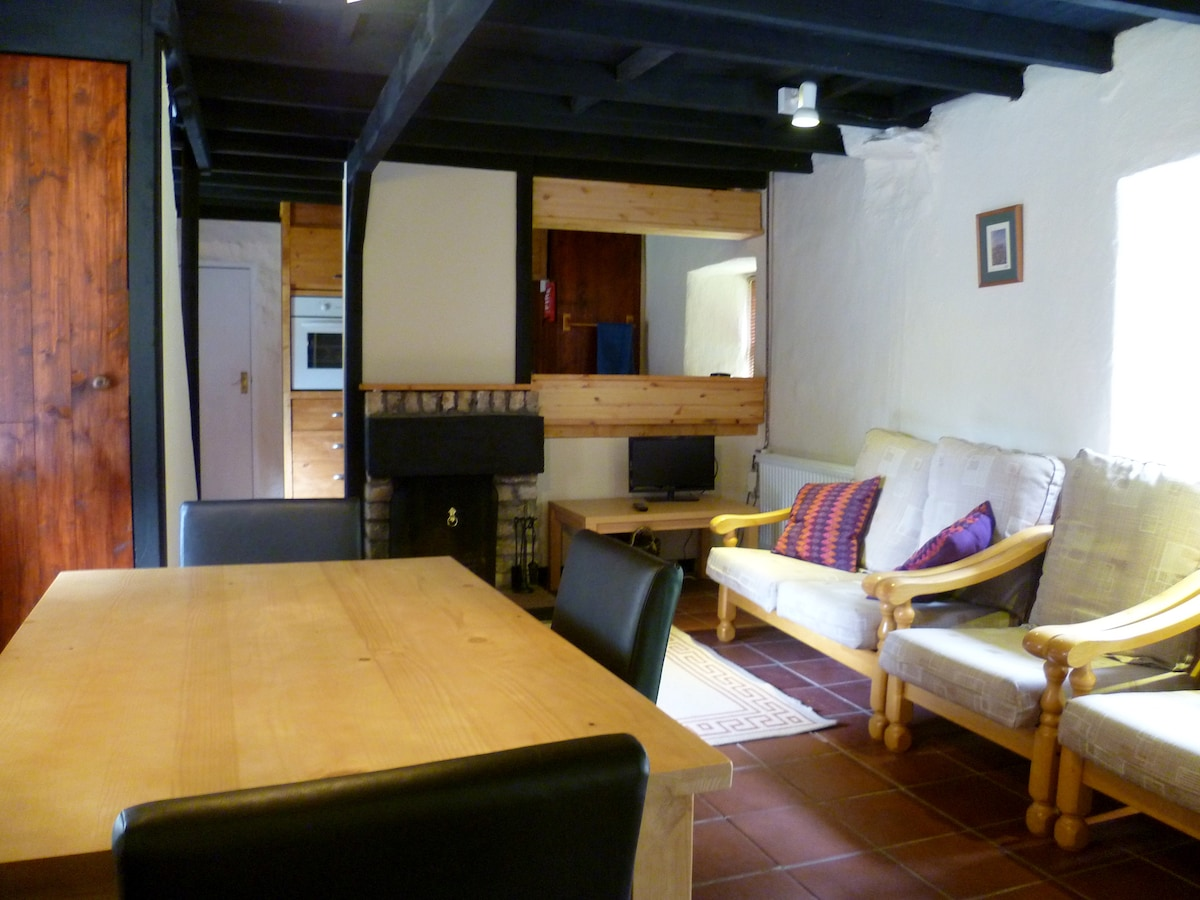 Fully equipped galley kitchen, open fire, comfy seating and dining table.