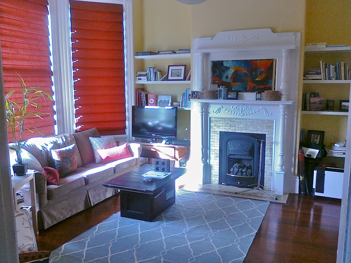 Living room with HDTV, gas fireplace, tree-lined street views; sofabed and crown molding