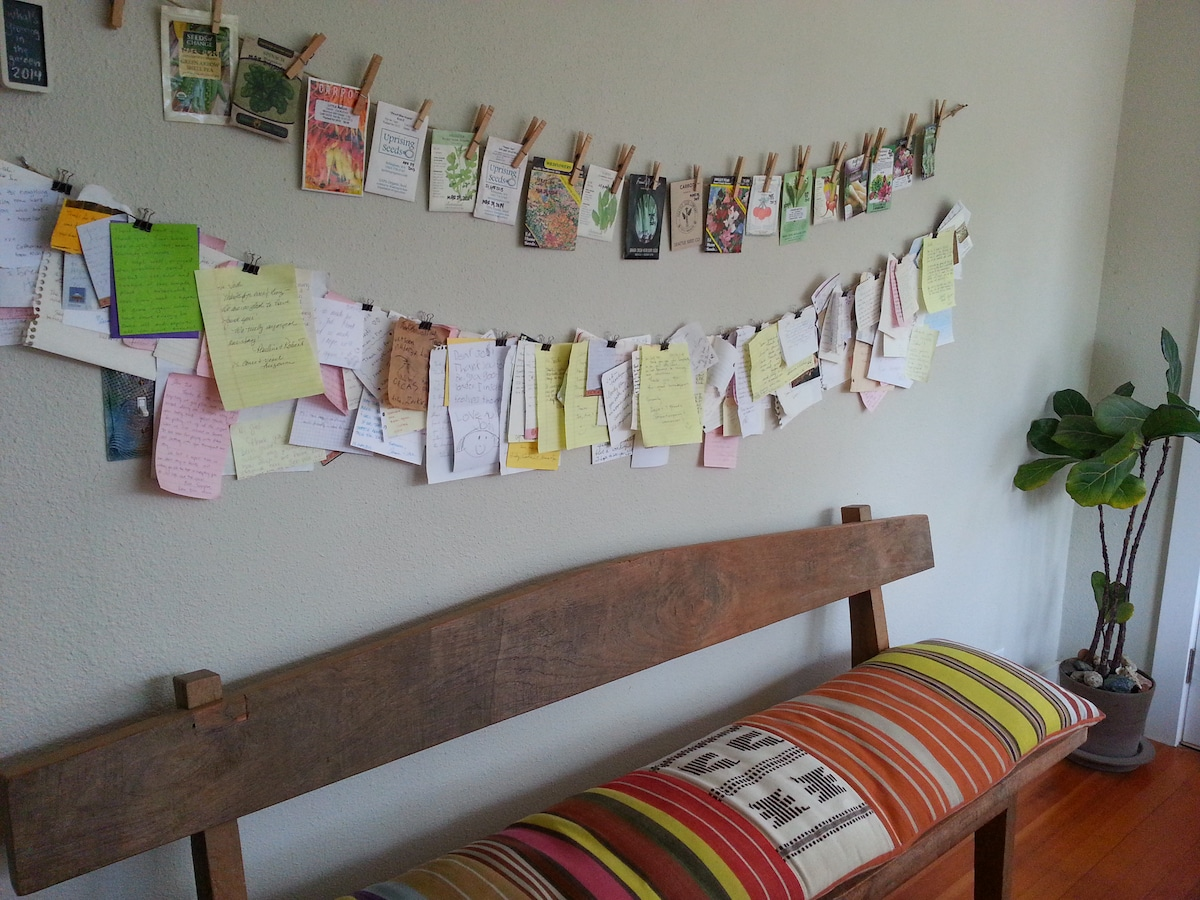 seed packets from this year's garden as well as notes from guests decorate a wall in the living room.