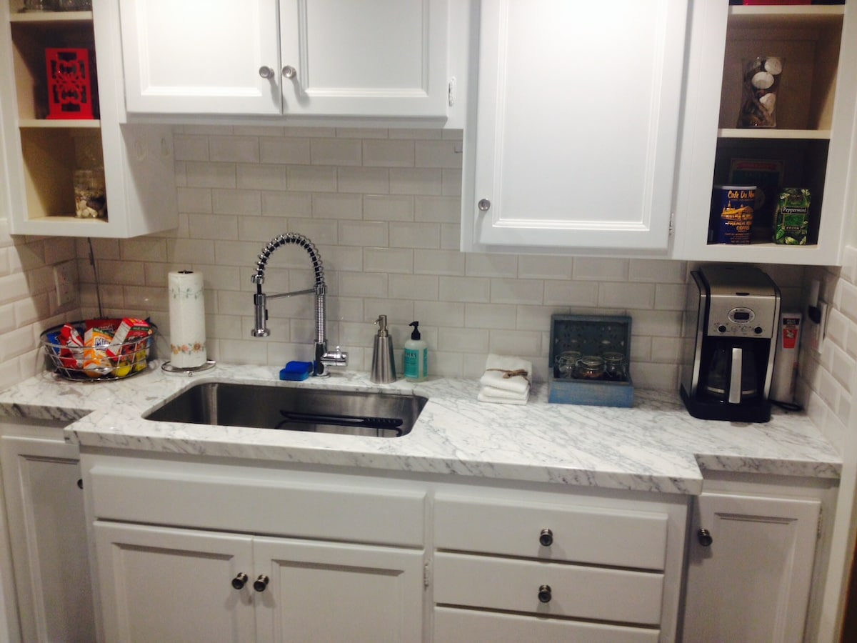The kitchenette with Italian carrera marble countertops, storage and a fridge. Coffee maker, kettle, toaster and microwave are tucked away out of sight......