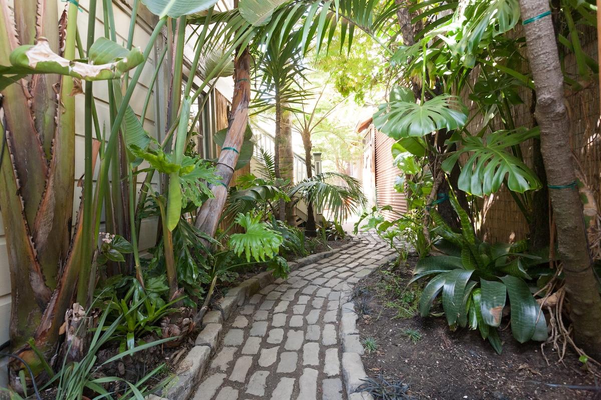 Entrance from the street through a tropical garden