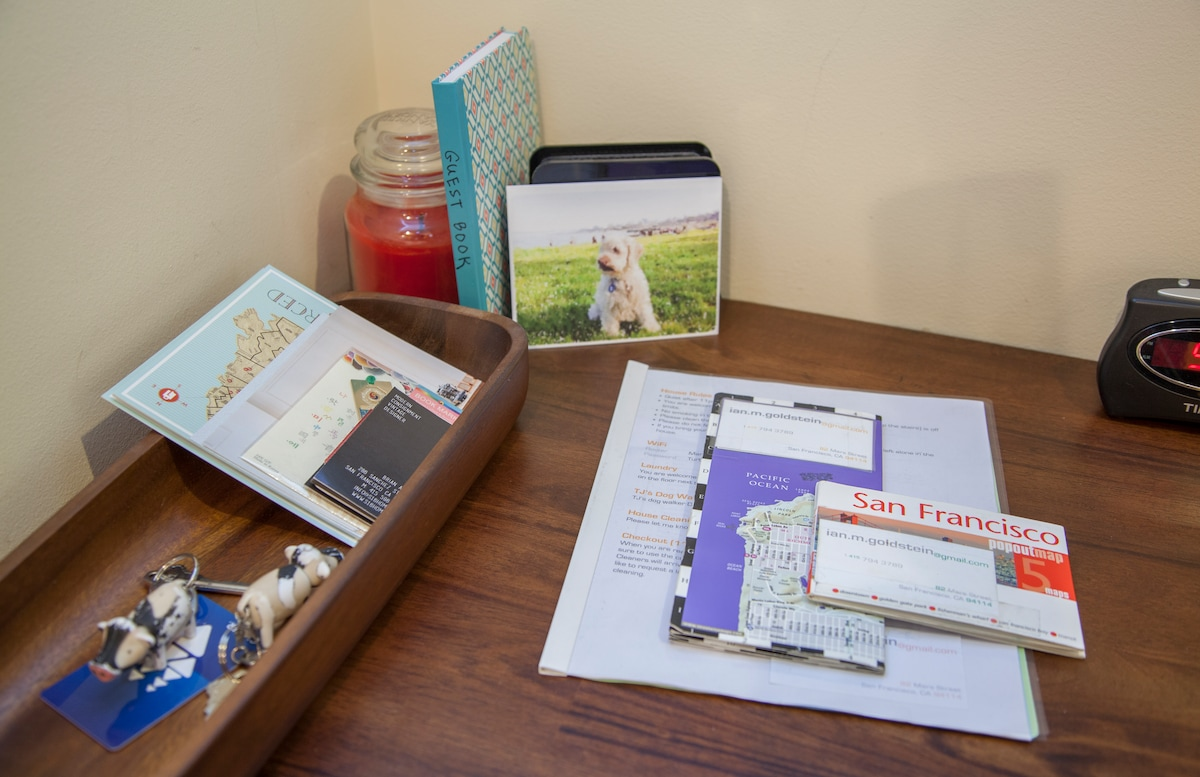 Your desk with house manual, city maps, free postcards, alarm clock, and some business cards from some local restaurants I love.