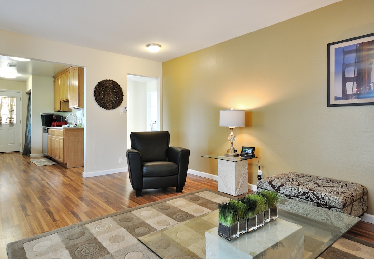 The living room features hardwood floors, classy furniture, and tasteful decor.