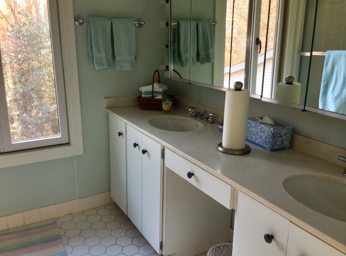 En suite bathroom with double sinks, tub and shower
