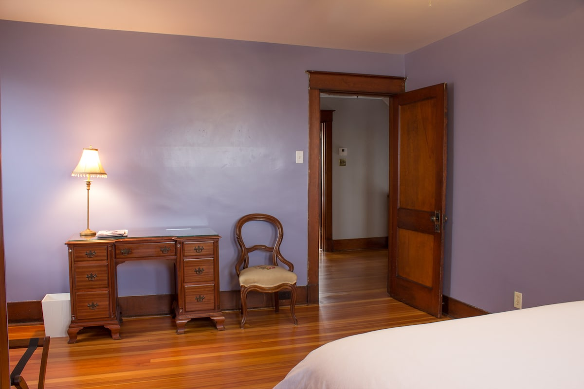 Huge guest bedroom with desk and chair.