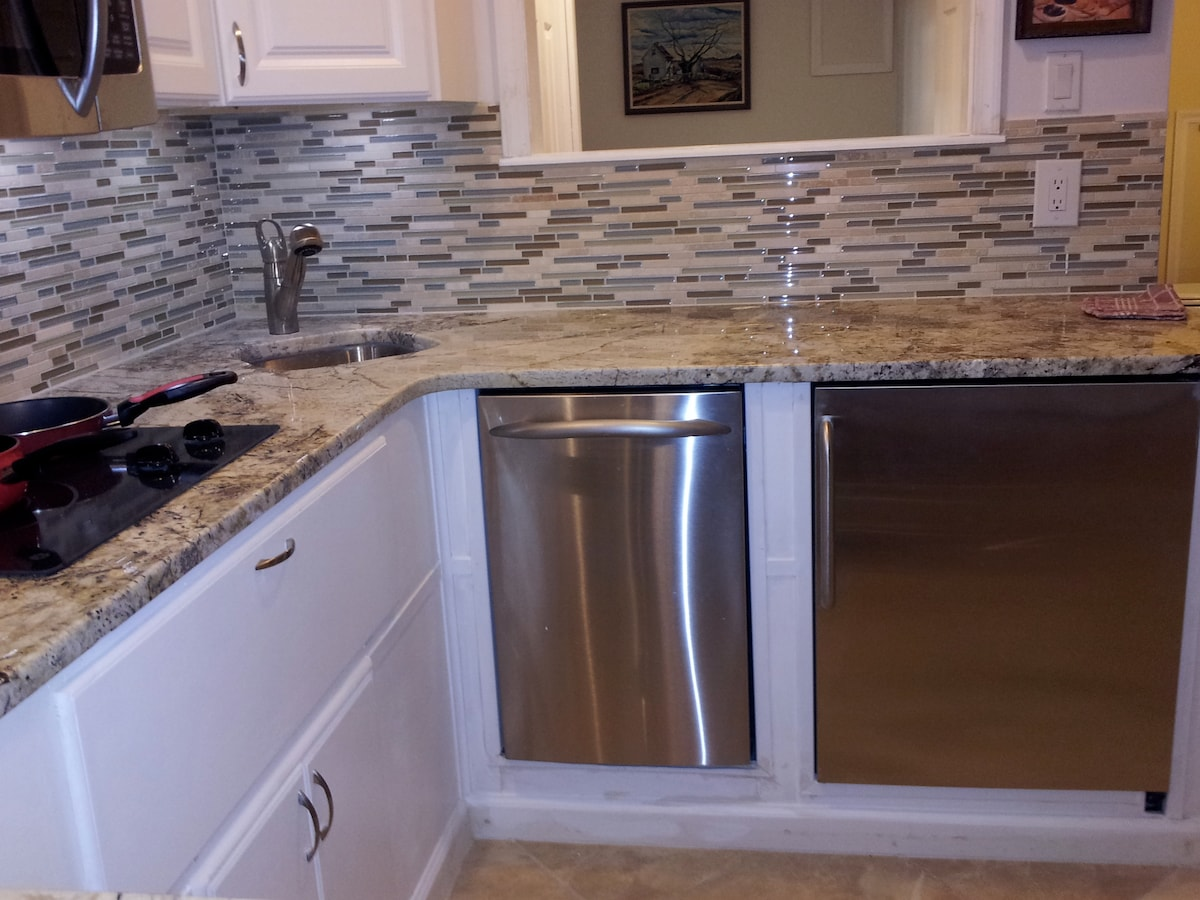 Another view of dishwasher and refrigerator.