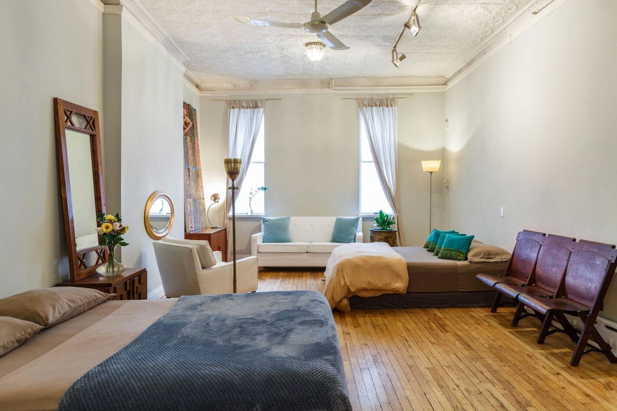 The front: Glamorous, huge bedroom with a new queen size bed, a full size bed and the white leather couch folds out to a full size bed. Antique wooden bench to set your luggage, authentic high tin ceilings drooping with chandeliers floating on wood floors
