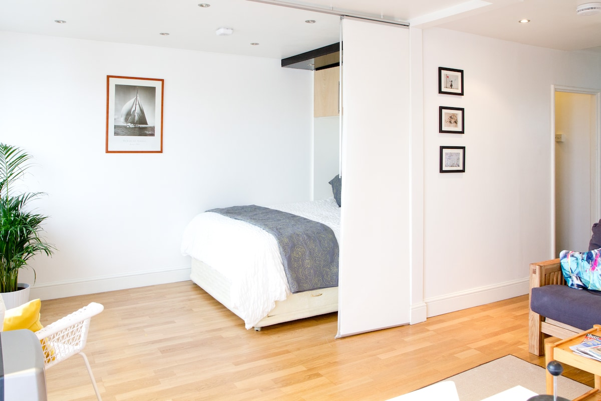 The bedroom area has dividing wall panels to give you extra privacy night or day.  It extends so far that it completely hides the bed from the sitting room.