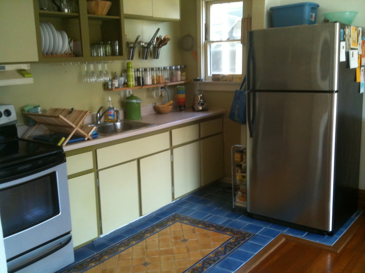 the kitchen is part of the living room with hand made tile floor area