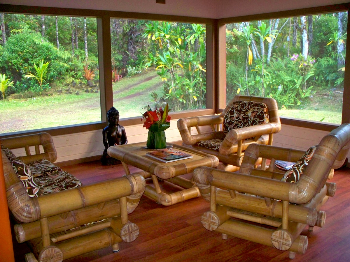 The living room sits among an old growth Ohia forest and jungle greenery  Oversized bamboo furniture for comfortable lounging.