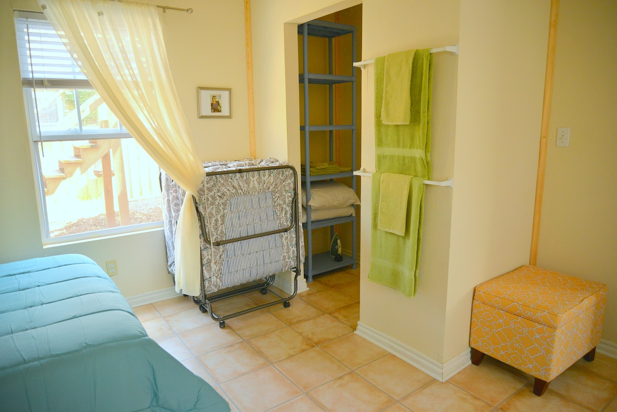 Shows 1, bright, sunny window looking onto the garden and 1 of the 2 folding twin cots.