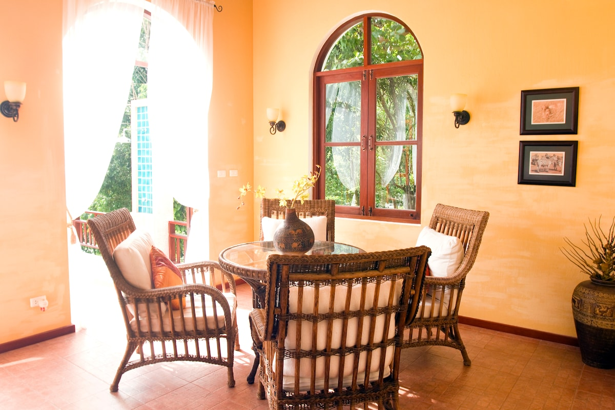 Sitting Area of the open living room with French doors to the pool deck and views of the sea and garden