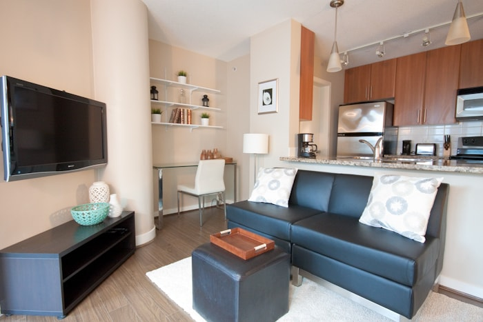 Living space with wall mounted LCD TV, off office nook desk area and wall shelving decor