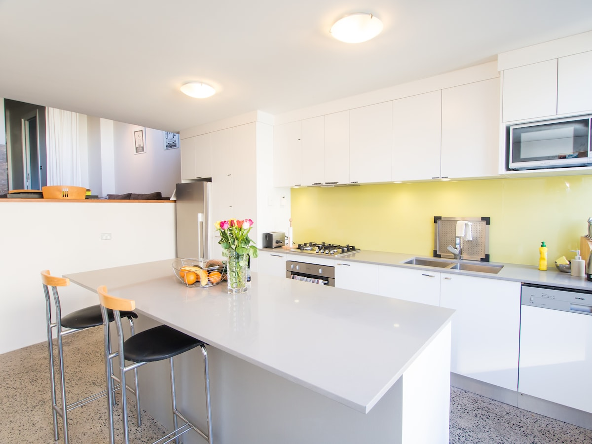 Full Size Kitchen with Island Bench, Gas Oven & Cooktop and Dishwasher. The Floor is Heated