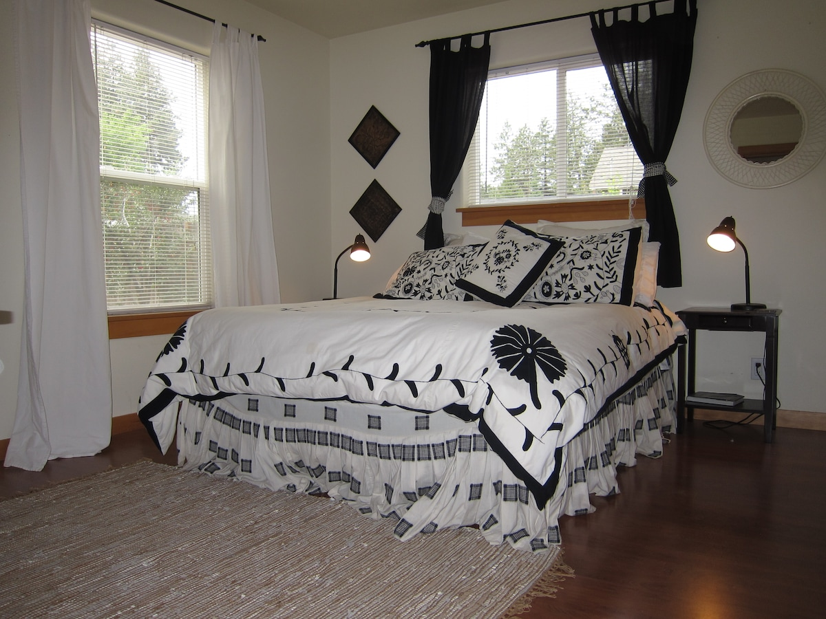 Ecclectic, light and airy guest bedroom with large walk-in closet and entrance to guest bathroom.