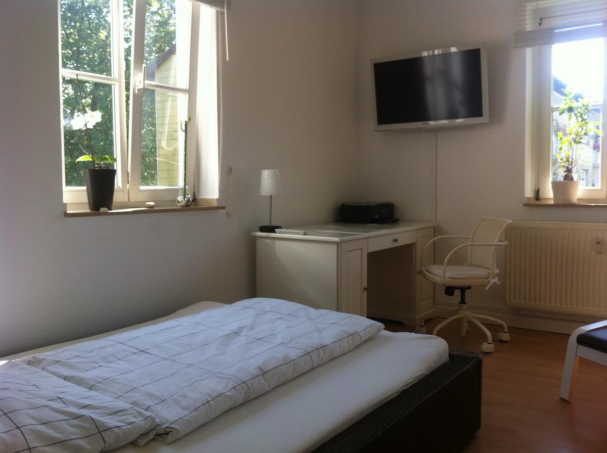 Bett und Schreibtisch. / The guest room