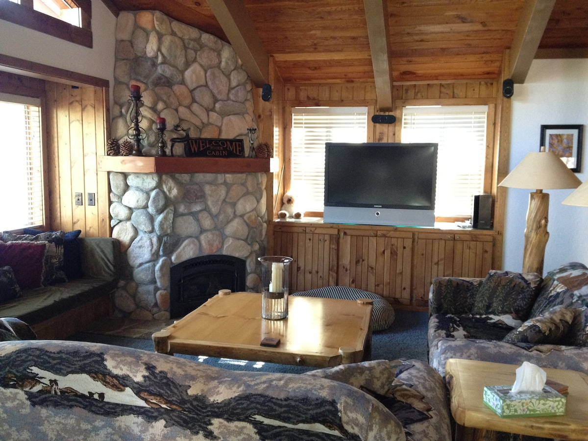 Gorgeous living room with stone gas fireplace and big screen TV