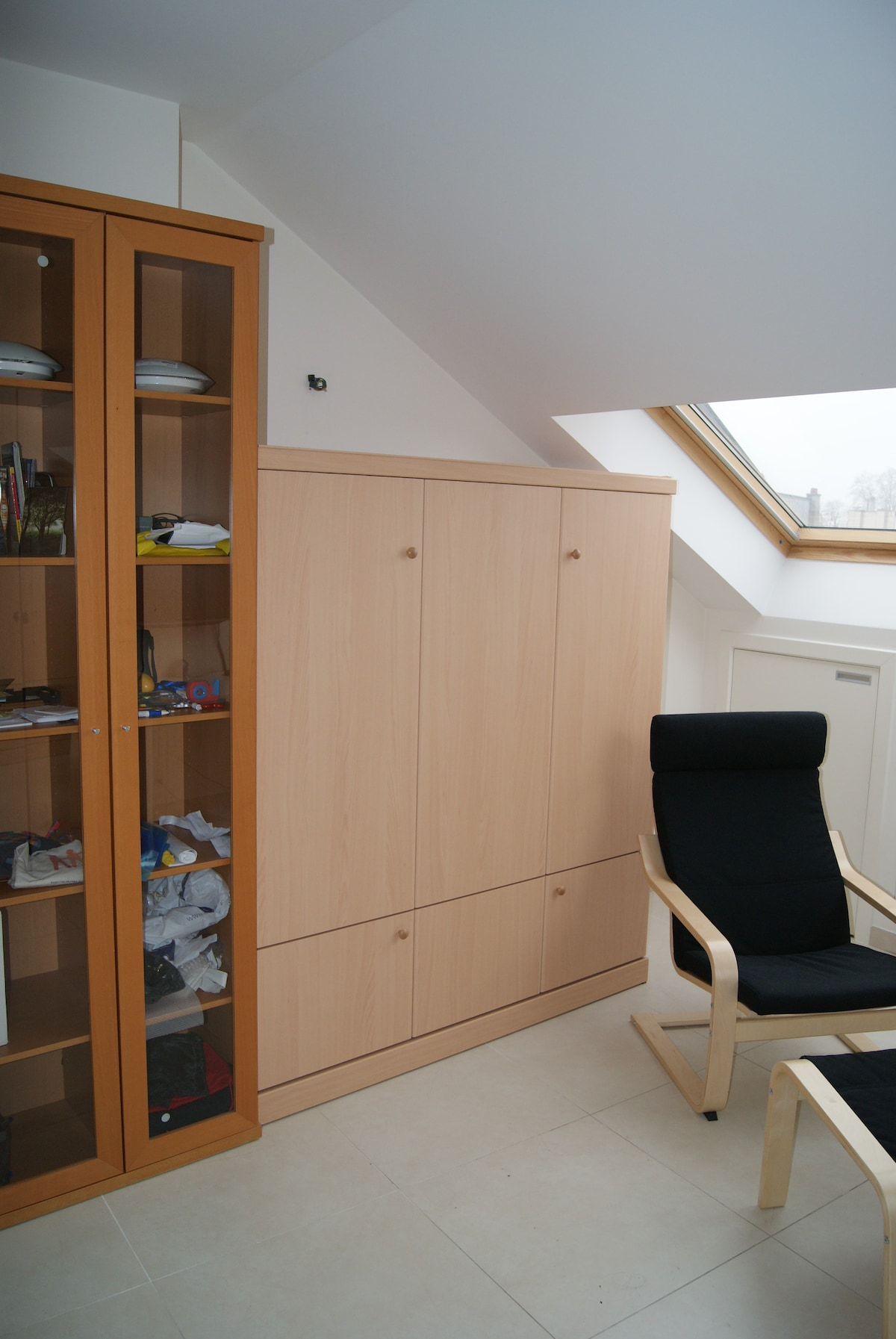 View with wardrobe bed folded away, allows space for armchair and footrest for reading or watching TV.