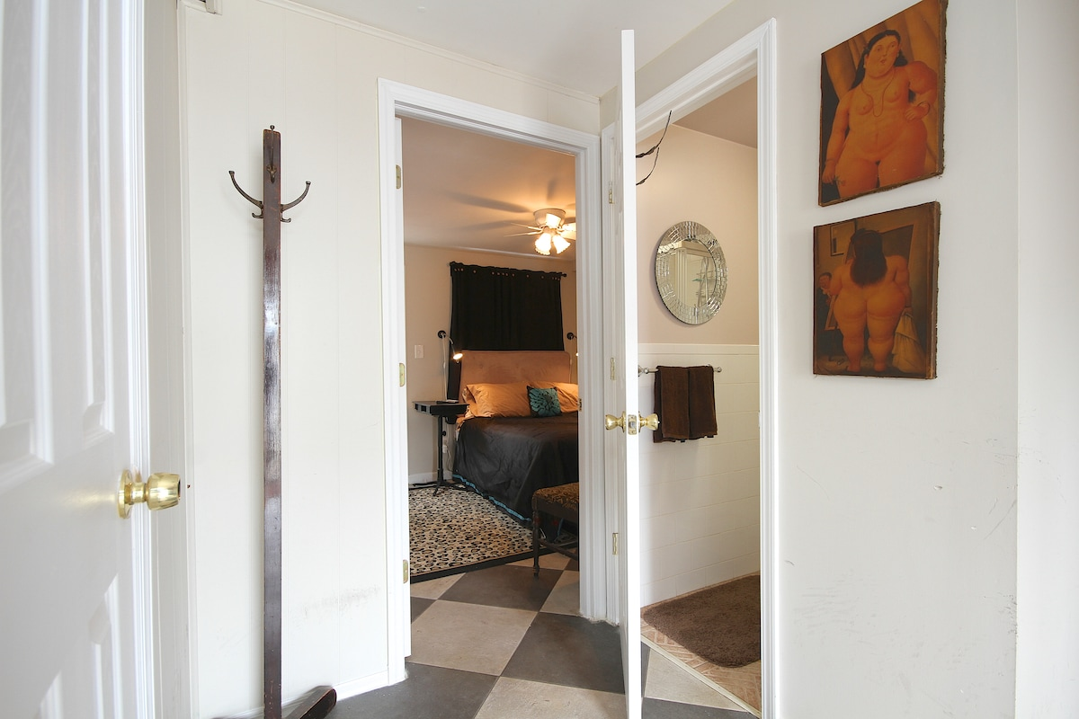 Older photo of bedroom and private bathroom from front entryway area.