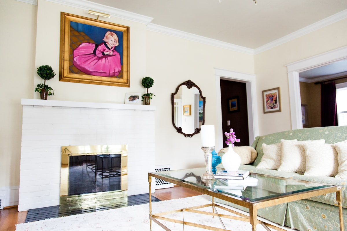 The formal living room is framed by a gas fireplace and fine oil paintings.