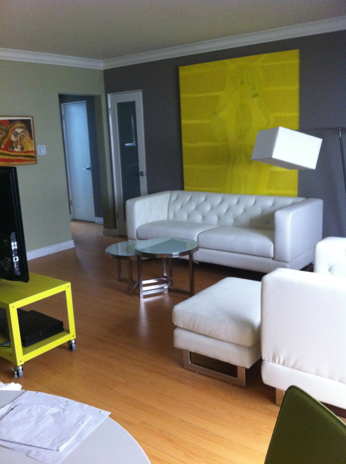 """The living room area with white leather sofa and chair, , 50"""" HDTV, glass doors, great art...very stylish"""