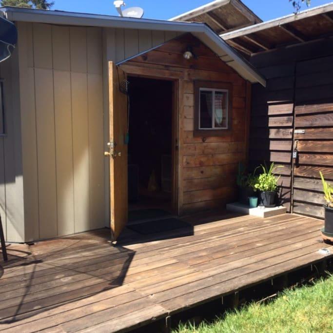 Studio door opens to private, outdoor yard and deck