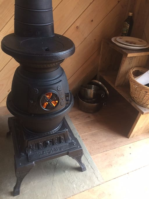 Cast iron pot-belly woodstove warms cabin and has small cook-top surface for heating water for coffee, warming food.