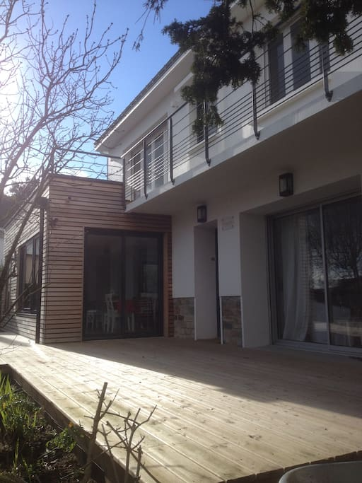 Le séjour, la salle à manger et la cuisine donnent sur une grande terrasse en bois