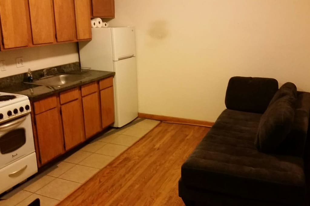 Full kitchen with fridge, stove,microwave, dishes, utensils, and sofa/bed