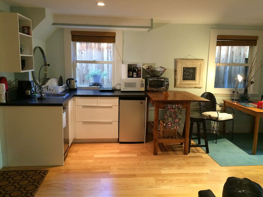 Efficiency kitchen with sink, dishwasher, microwave, toaster oven, induction cooktop, small fridge and all utensils and tableware provided.