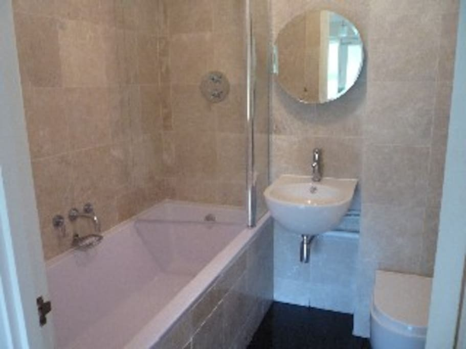 Bathroom with large bathtub and shower over