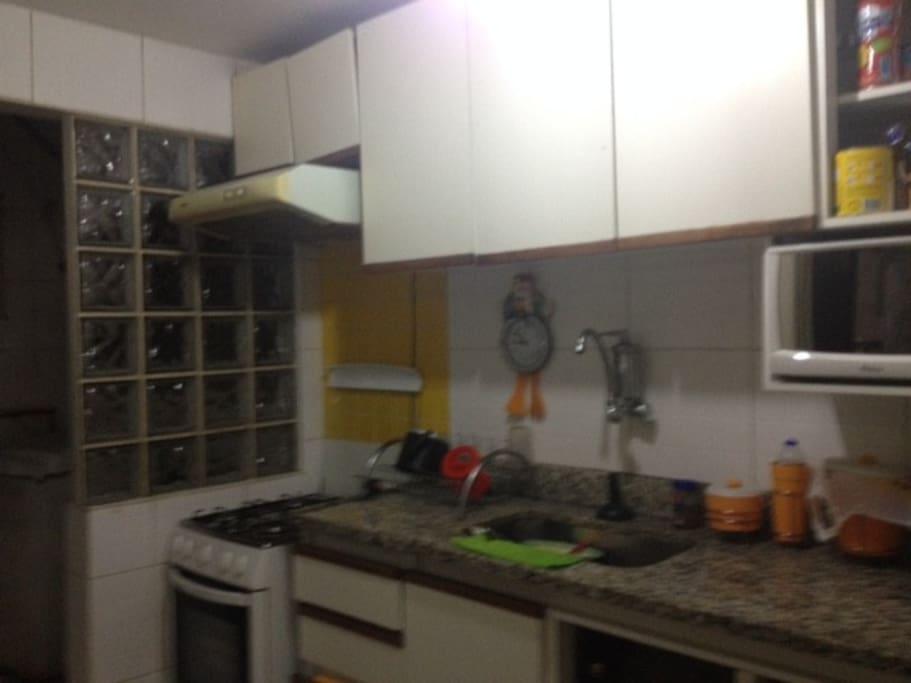 Cozinha com armários, fogão, geladeira e microondas