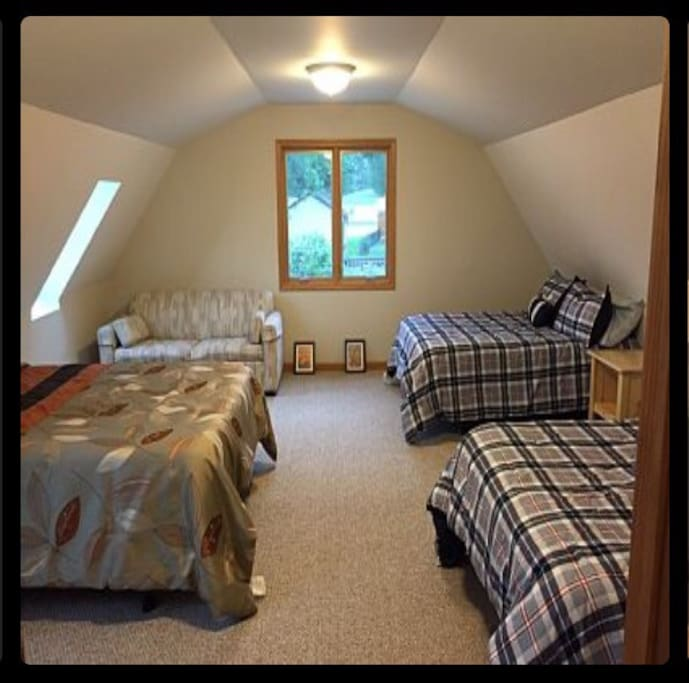 Large bedroom above garage with 3 queen size beds and a sleeper sofa.